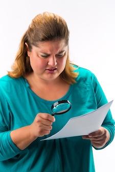 Donna che osserva tramite la lente d'ingrandimento o la lente di ingrandimento