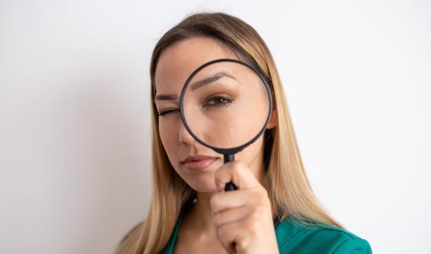 Donna che osserva tramite la lente d'ingrandimento