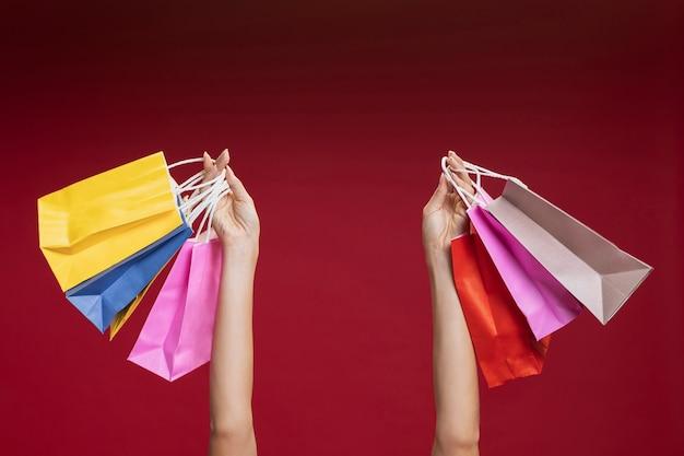 Donna che ostacola il suo primo piano dei sacchetti della spesa