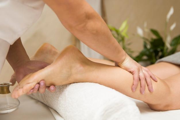 Donna che ottiene massaggio delle gambe nel centro termale