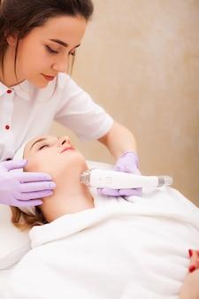 Donna che ottiene massaggio hardware gpl presso la clinica di bellezza. estetista professionista che lavora