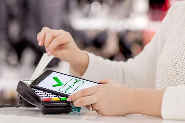Donna che paga fattura tramite smartphone utilizzando la tecnologia nfc nel ristorante, caffetteria, bar