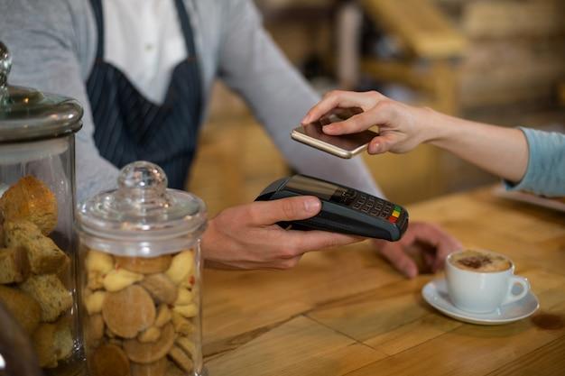 Donna che paga fattura tramite smartphone utilizzando la tecnologia nfc