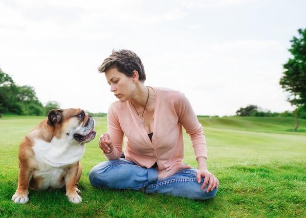 Donna che parla con bulldog rosso sul prato il giorno soleggiato in parco