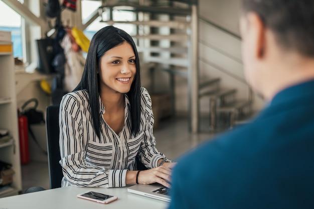 Donna che parla con il cliente nel negozio di auto.