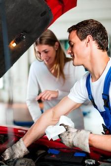 Donna che parla con meccanico di automobile nell'officina riparazioni