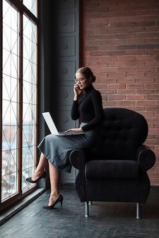Donna che parla sopra il telefono con il computer portatile