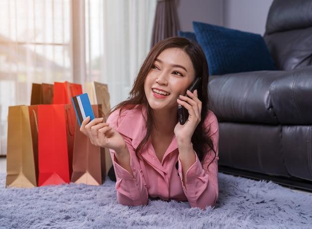 Donna che parla su smartphone per lo shopping online con carta di credito in salotto