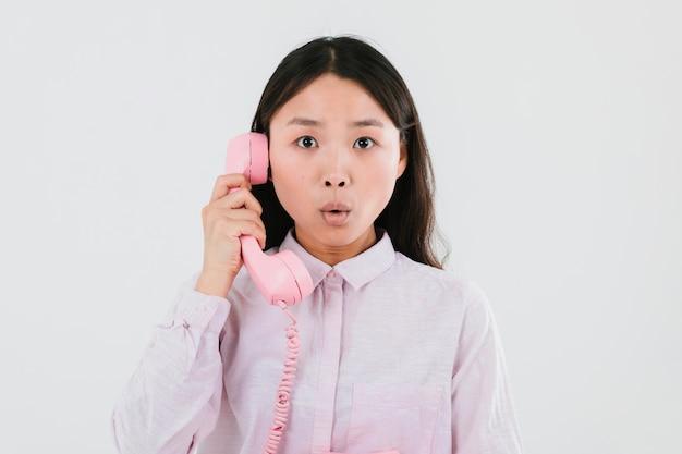 Donna che parla su un telefono rosa