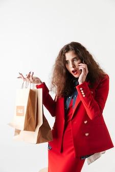 Donna che parla sul telefono cellulare e che tiene i sacchetti della spesa di carta