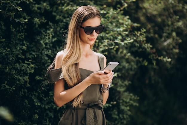 Donna che parla sul telefono in parco