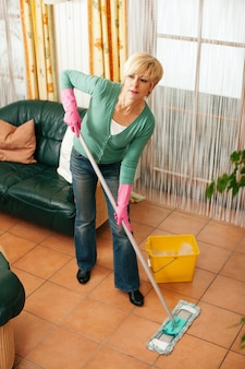 Donna che passa lo straccio sul pavimento nella sua casa