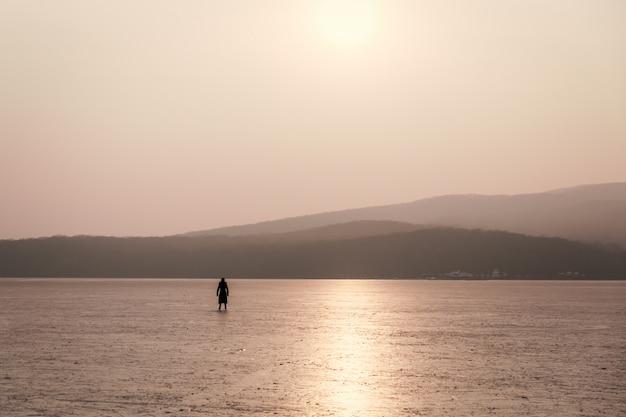 Donna che pattina su una baia congelata al tramonto
