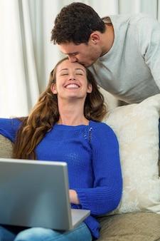 Donna che per mezzo del computer portatile e dell'uomo che bacia sulla sua fronte mentre per mezzo del computer portatile nel salone