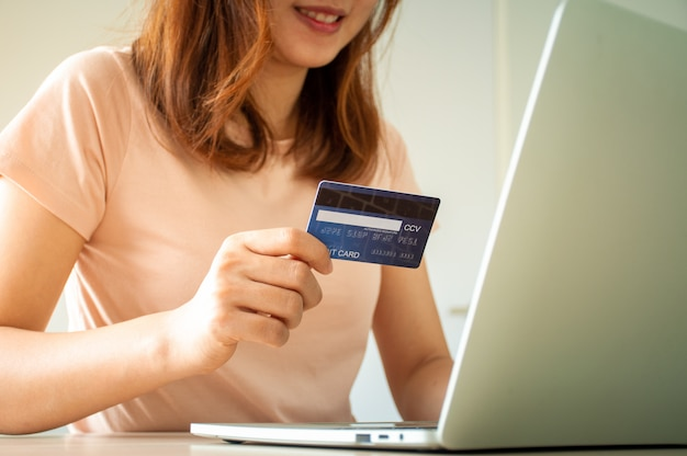 Donna che per mezzo del computer portatile e della carta di credito per ordinare i prodotti online