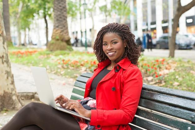 Donna che per mezzo del computer portatile e sorridere