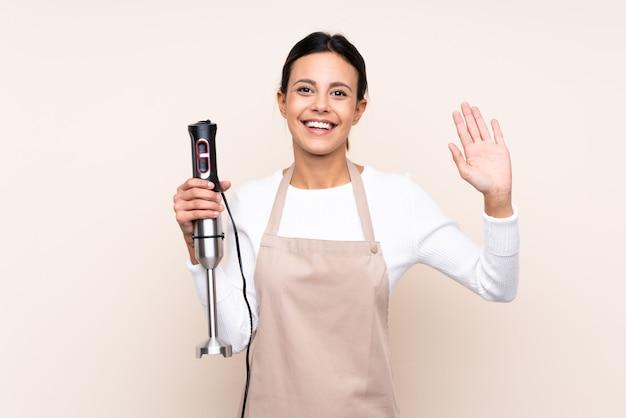 Donna che per mezzo del miscelatore della mano sopra la parete che saluta con la mano con l'espressione felice