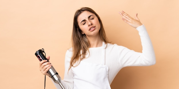 Donna che per mezzo del miscelatore della mano sopra la parete isolata con l'espressione stanca e malata