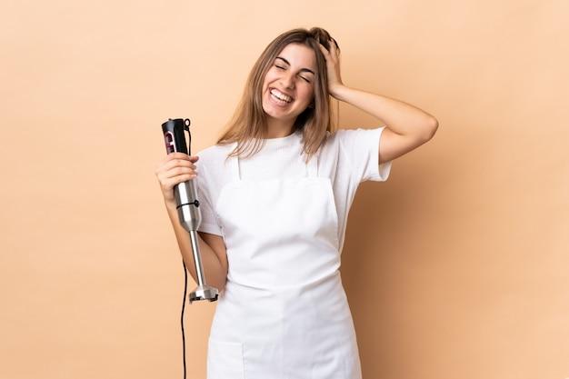 Donna che per mezzo del miscelatore della mano sopra la risata isolata della parete