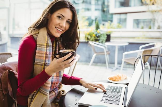 Donna che per mezzo del suo computer portatile e bevendo caffè