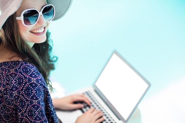 Donna che per mezzo del suo computer portatile
