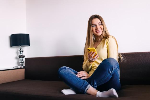 Donna che per mezzo del suoi cellulare e invio di messaggi di testo mentre sedendosi su così