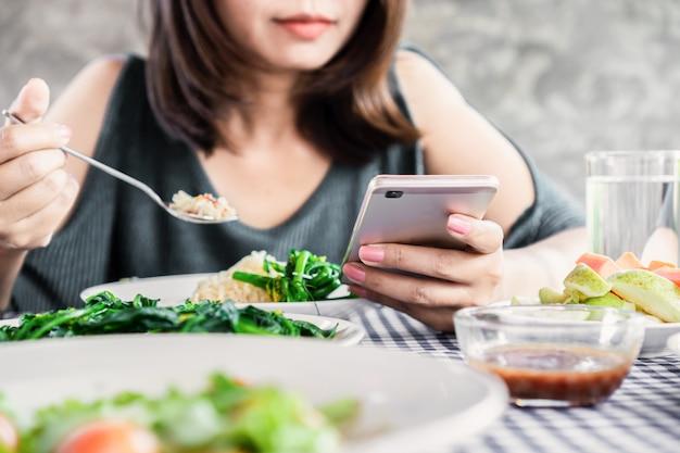 Donna che per mezzo del telefono cellulare mentre cenando