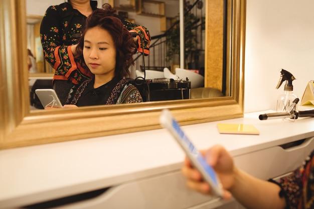 Donna che per mezzo del telefono cellulare mentre raddrizzando i capelli