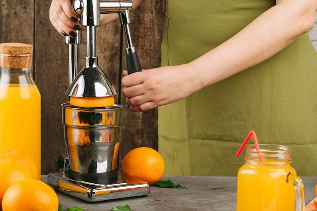 Donna che per mezzo dell'apparato degli spremiagrumi arancio a casa
