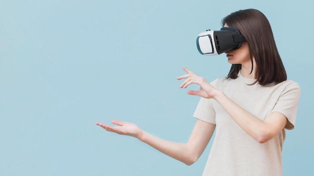 Donna che per mezzo della cuffia avricolare di realtà virtuale con lo spazio della copia