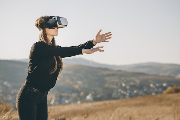 Donna che per mezzo della cuffia avricolare di realtà virtuale e guardando intorno alla mostra interattiva di tecnologia