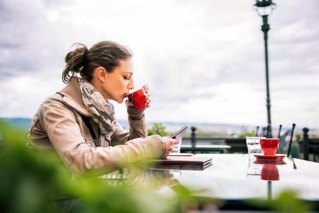 Donna che per mezzo dello smart phone e bevendo caffè