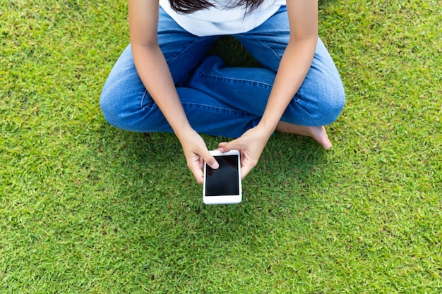Donna che per mezzo dello smart phone mobile sull'erba per il rilassamento con i social media