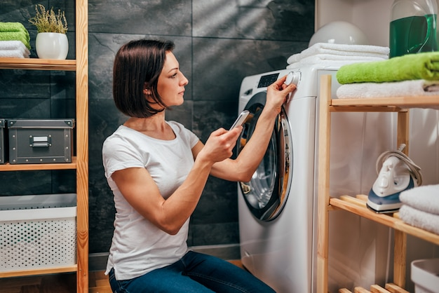 Donna che per mezzo dello smart phone per controllare lavatrice