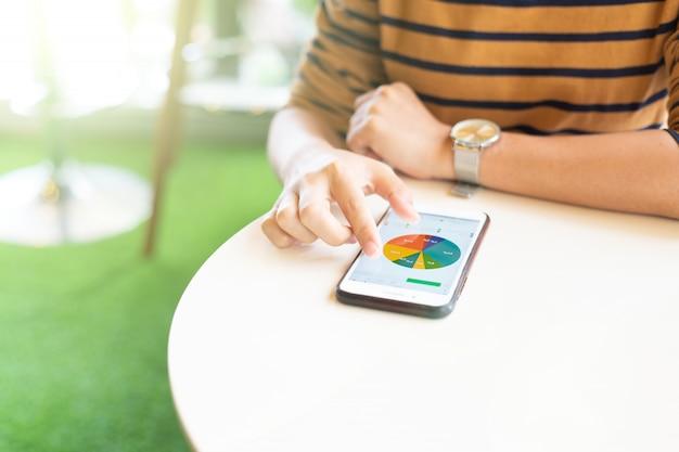 Donna che per mezzo dello smart phone per verificare i dati al caffè