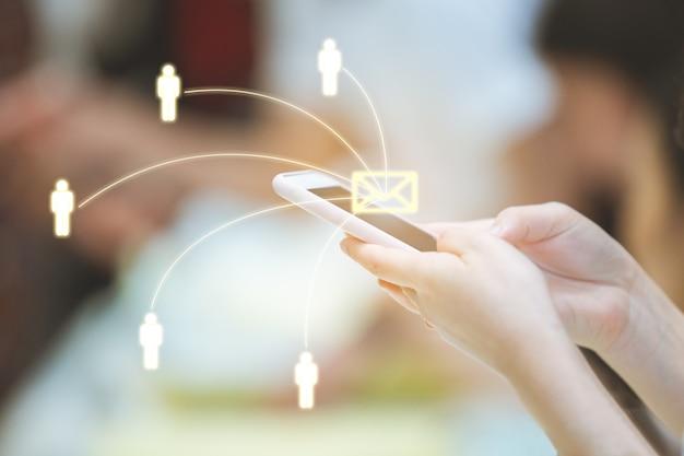 Donna che per mezzo dello smartphone che invia messaggio dall'e-mail ad altre persone con la rete.