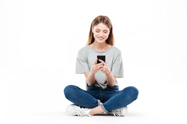 Donna che per mezzo dello smartphone e sedendosi sul pavimento