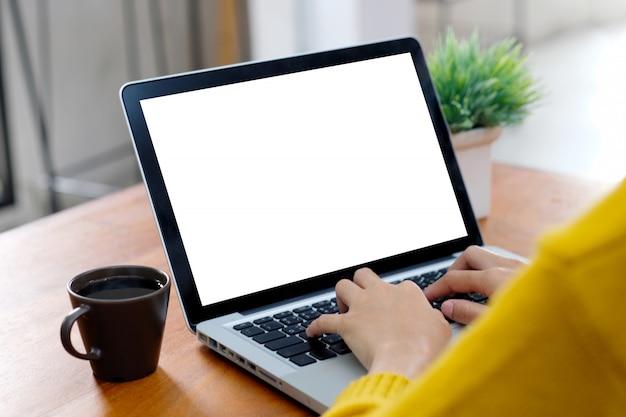 Donna che per mezzo di un computer portatile con lo schermo in bianco
