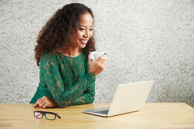 Donna che per mezzo di un computer portatile per guardare un film