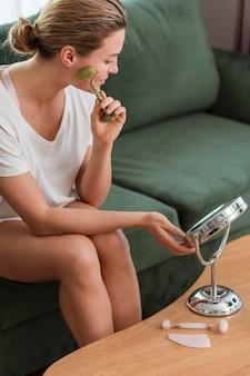 Donna che per mezzo di un dispositivo per la vista di massaggio del viso alta