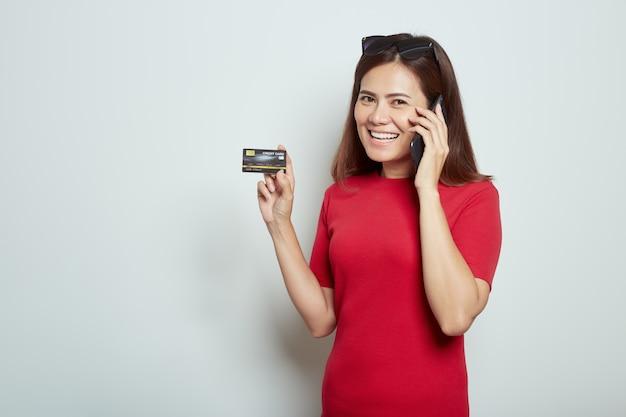 Donna che per mezzo di un telefono cellulare con la carta di credito