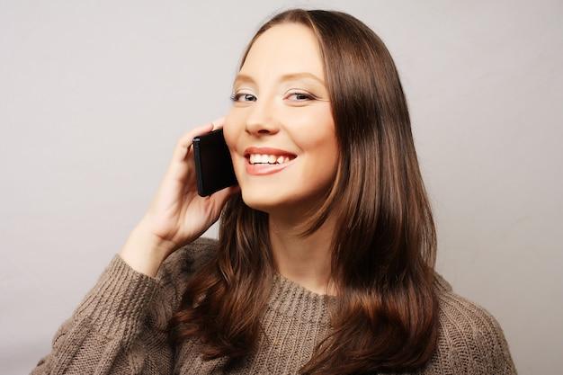 Donna che per mezzo di un telefono mobile isolato su una priorità bassa bianca