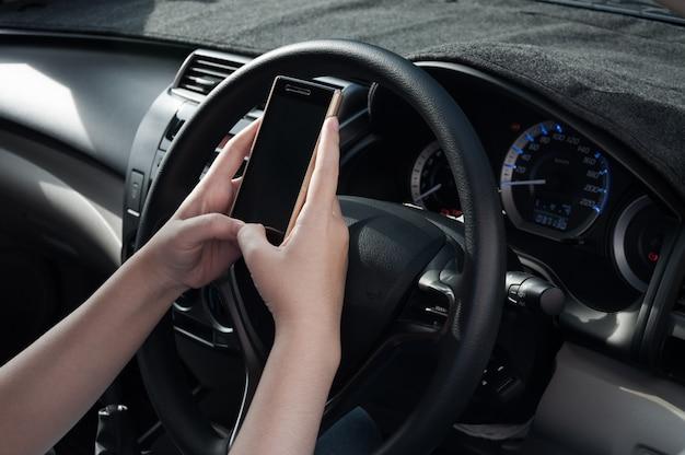 Donna che per mezzo di uno smartphone mentre guidando un'automobile. dipendenza dai social media