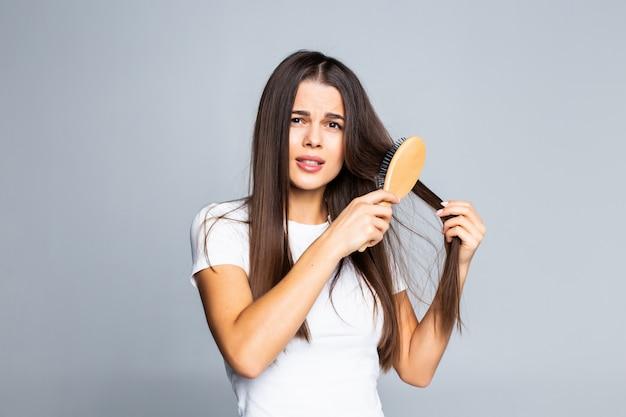 Donna che pettina i suoi capelli isolati su un bianco