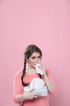 Donna che piange e usando la scatola di tovaglioli