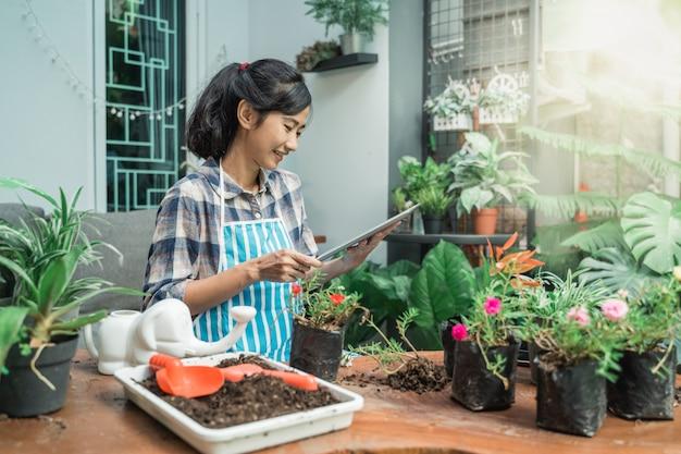 Donna che pianta fiore a casa