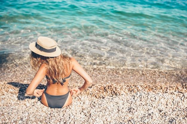 Donna che pone sulla spiaggia in cappello di paglia godendo le vacanze estive guardando il mare