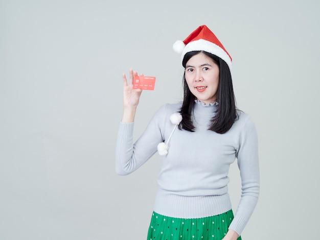 Donna che porta a disposizione il cappello di santa che mostra la compera delle carte di credito