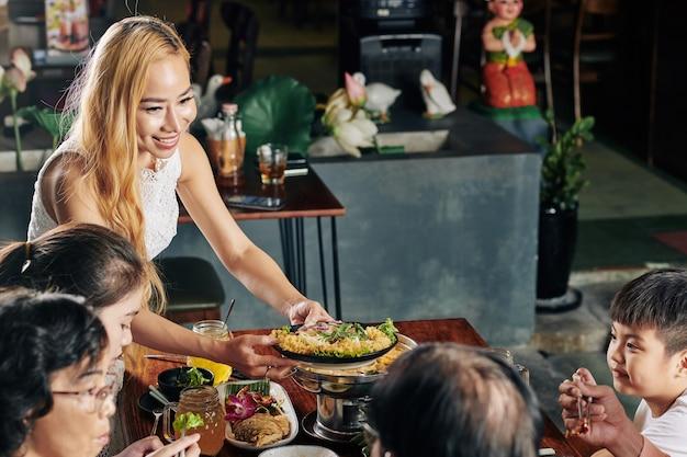 Donna che porta il piatto al tavolo