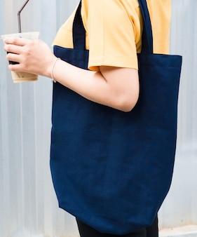 Donna che porta un mockup blu del sacchetto della spesa